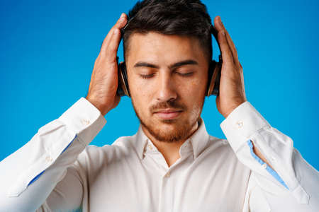 Handsome young mixed-race man listening to music with blue headphones