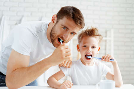 Dad and little son brushing teeth together 版權商用圖片