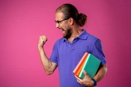 Overjoyed funny bearded man in glasses celebrating success