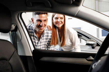 Young couple choosing their new car in a car shop Imagens