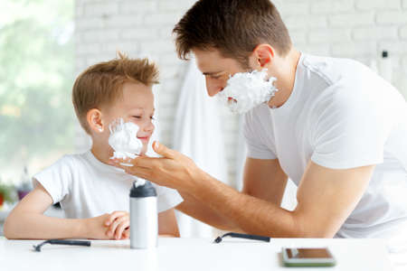 Father teaches his little son how to shave face Фото со стока
