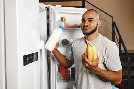 African american man taking food from a fridge in his house