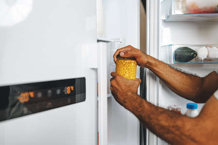 Male hands taking canned corn jar from fridge