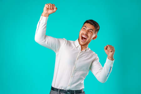 Portrait of excited, successful man raising hands up