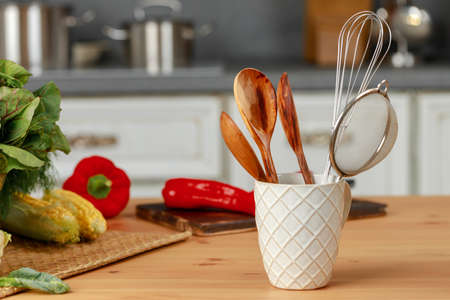 Kitchenware utensils in a cup on kitchen table Imagens