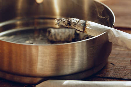 Lighted cigarette in a metal ash tray close up