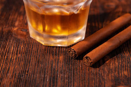 One glass of whisky and cigar on wooden table
