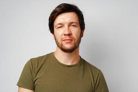 Portrait of a serious pensive young man against grey background Reklamní fotografie