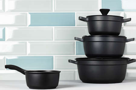 Set of black cookware on kitchen counter