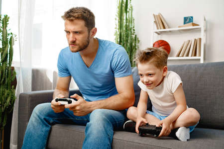 Father and his little son playing video games together at home