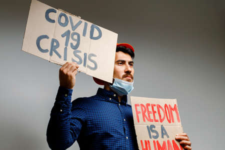 Covid-19 crisis placard in hands of protester