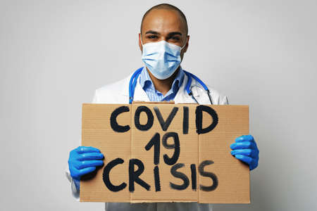 Covid-19 crisis placard in hands of protester man. 版權商用圖片