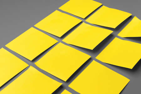 Yellow adhesive notes on gray background close up