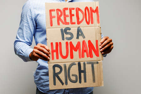 Freedom is a human right placard in hands of protester Imagens