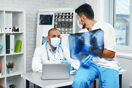 Two male doctors examine an x-ray of lungs in hospital