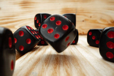 Macro of black tossed dice on wooden background