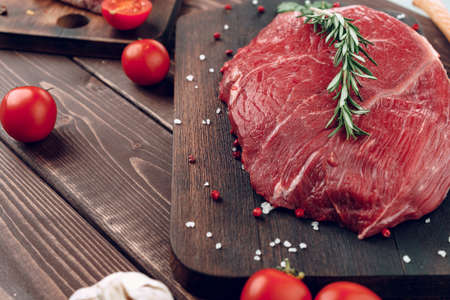Raw beef steak with rosemary and spices on wooden board
