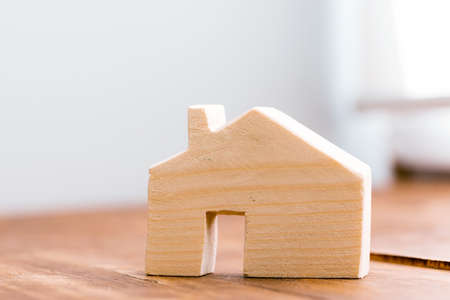 Wooden house miniature on wooden surface close up 写真素材