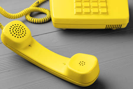 Yellow .landline phone on gray background top view