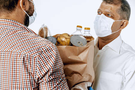 Delivery man in face mask and gloves. Food delivery, online shopping concept while coronavirus pandemia
