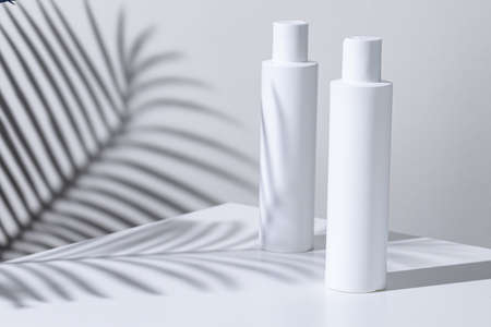 White plastic skincare tubes on a background of tropical plant shadow Banque d'images