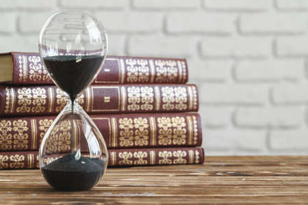 Vintage hourglass against a stack of old books Imagens
