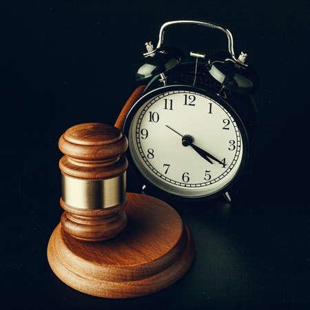 Wooden judge hammer with alarm clock on black background Stockfoto