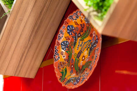 Colorful ceramic painted plates hanging on the red wall