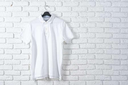 White t-shirt hanging on hanger against brick wall