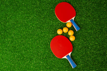 Table tennis rackets and ball on grass Foto de archivo