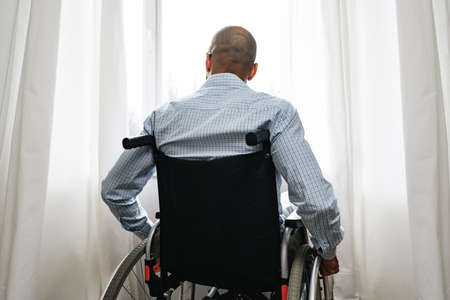African american man in wheelchair sitting near the window alone at home Imagens