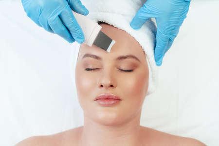 Beautiful woman receiving ultrasonic face cleaning in beauty salon