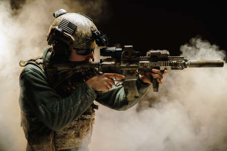 Special forces soldier aiming with his rifle in fog