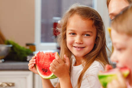 Smiling little girl eating a slice of watermelon in kitchen