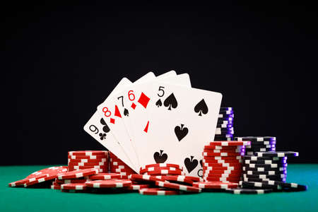 Poker chips and playing cards on black background Stockfoto