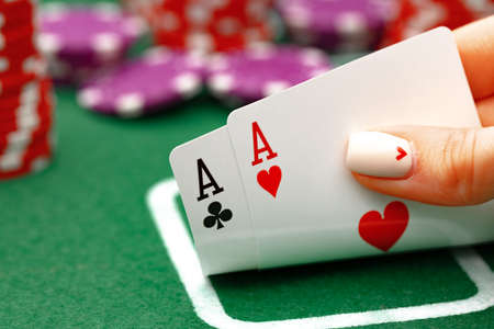 Female holding playing cards, playing poker at green table Stock Photo