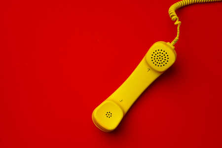 Yellow landline phone on red background top view