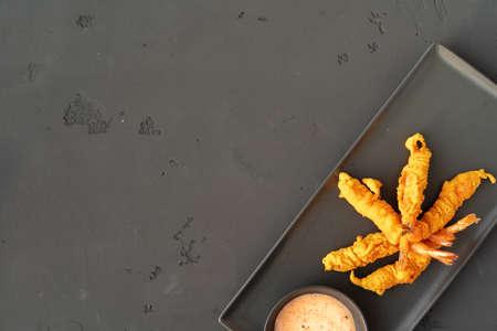 Deep fried crispy shrimps with sauce on black ceramic plate Standard-Bild