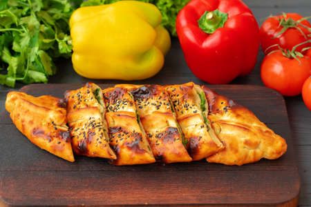 Stuffed bread, turkish pie with herbs on wooden board Standard-Bild