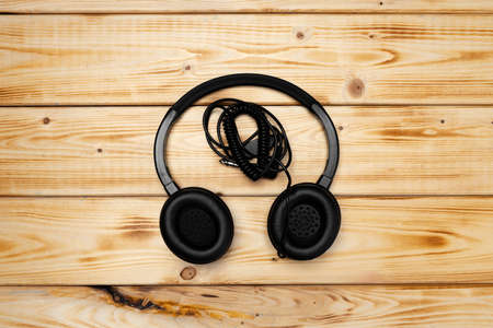 Black headphones with wire on wooden background Standard-Bild