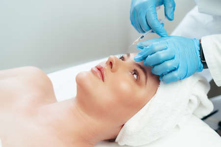 Portrait of a beautiful woman having an injection of botox in her face