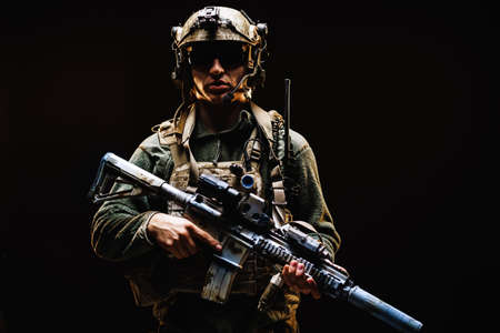 Special forces soldier with rifle on black background