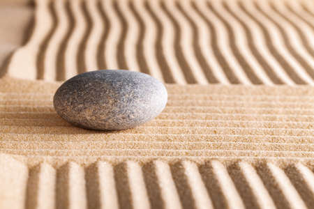 Japanese zen garden with stone in raked sand