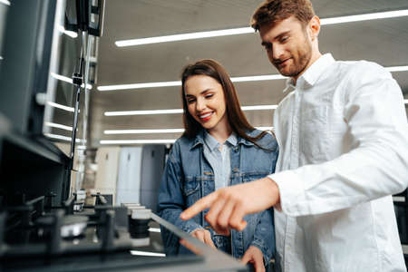 Young couple choosing new gas stove in home appliances store