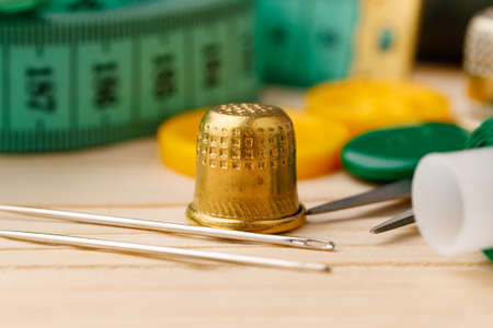 Thimble and measuring tape on wooden table