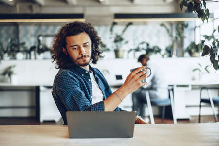 Young businessman is using laptop and holding a cup of coffee in office