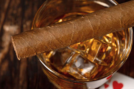 Playing poker with whiskey and cigars on table
