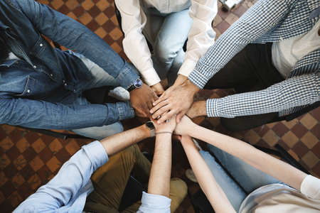 Top view of diverse people hands holding together in circle, hands stack