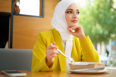 Young muslim woman in hijab having a lunch in cafe