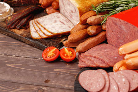 Assortment of meat and sausage on wooden surface